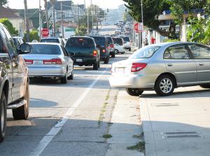 """Autokeskne tänav, kus parkimine on """"laienenud"""" ka jalakäijate alale. Allikas: Flickr kasutaja Richard Masoner."""